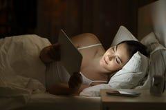 使用在床上的轻松的女孩一种片剂夜 库存图片