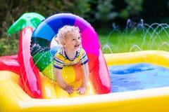 使用在庭院游泳池的小男孩 库存图片