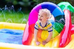 使用在庭院游泳池的小男孩 免版税库存照片