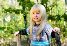 使用在庭院的微笑的小白肤金发的女孩 图库摄影