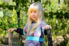 使用在庭院的微笑的小白肤金发的女孩 库存照片