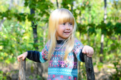 使用在庭院的微笑的小白肤金发的女孩 免版税库存图片