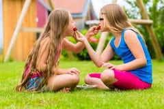 使用在庭院里的姐妹吃草莓 免版税库存照片