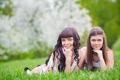使用在开花的树的背景的绿草的两个愉快的女孩 库存图片