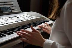 使用在您的智能手机的apps白色衬衣的女孩是被实践的使用在一架电子钢琴 图库摄影