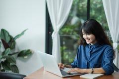 使用在手提电脑的亚裔妇女在窗口附近在咖啡馆餐馆,数字时代生活方式,使用Technolgy概念,co工作 库存图片