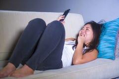 使用在手机微笑的放松的在家说谎的年轻甜愉快和相当亚裔韩国妇女互联网社会媒介app沙发 免版税库存照片