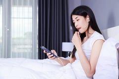 使用在手机的妇女耳机设备在床上在卧室 库存图片