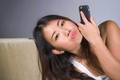 使用在手机的年轻甜愉快和相当亚裔韩国妇女互联网社会媒介app在家摆在放松的沙发长沙发 库存照片