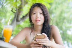 使用在手机的美丽的亚裔中国妇女互联网社会媒介坐在海滩享受夏天holid的餐馆手段 免版税库存图片