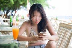 使用在手机的美丽的亚裔中国妇女互联网社会媒介坐在海滩享受夏天holid的餐馆手段 库存图片