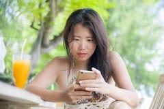 使用在手机的美丽的亚裔中国妇女互联网社会媒介坐在海滩享受夏天holid的餐馆手段 库存照片