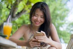 使用在手机的美丽的亚裔中国妇女互联网社会媒介坐在海滩享受夏天holid的餐馆手段 免版税图库摄影