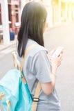 使用在手机的年轻亚裔旅行的博客作者或背包徒步旅行者路线应用发现需要的地址在城市 免版税库存照片