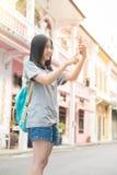 使用在手机的年轻亚裔旅行的博客作者或背包徒步旅行者路线应用发现需要的地址在城市 免版税图库摄影