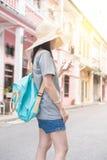 使用在手机的年轻亚裔旅行的博客作者或背包徒步旅行者路线应用发现需要的地址在城市 免版税库存图片