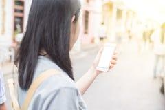使用在手机的年轻亚裔旅行的博客作者或背包徒步旅行者路线应用发现需要的地址在城市 库存照片