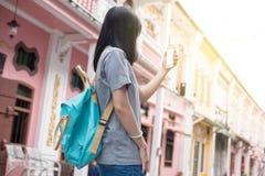 使用在手机的年轻亚裔旅行的博客作者或背包徒步旅行者路线应用发现需要的地址在城市 图库摄影
