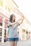 使用在手机的年轻亚裔旅行的博客作者或背包徒步旅行者路线应用发现需要的地址在城市 库存图片