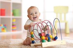 使用在托儿所的可爱的婴孩 获得愉快的健康的孩子与五颜六色的玩具的乐趣在家 免版税库存照片