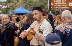使用在拥挤庆祝的传统英王乔治一世至三世时期被串起的乐器的年轻音乐家 库存照片