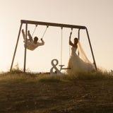 使用在摇摆的年轻夫妇剪影设置了在日落 免版税图库摄影
