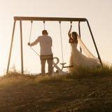使用在摇摆的年轻夫妇剪影设置了在日落 免版税库存图片