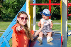 使用在摇摆的年轻美丽的母亲和女儿女婴愉快的家庭和乘驾在游乐园微笑 免版税库存照片