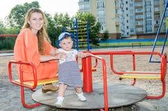 使用在摇摆的年轻美丽的母亲和女儿女婴愉快的家庭和乘驾在游乐园微笑 免版税库存图片