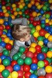 使用在操场五颜六色的球水池的男孩 免版税库存图片