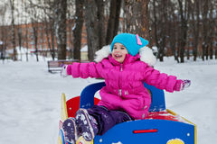 使用在操场的小女孩,获得使用的乐趣转动冬天的天在街道上的在公园 免版税库存照片