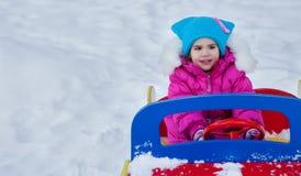使用在操场的小女孩,获得使用的乐趣转动冬天的天在街道上的在公园 免版税库存图片