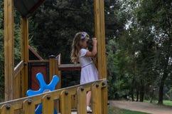 使用在操场的小迷人的女孩在公园,看通过玩具双筒望远镜 库存照片