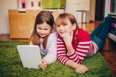 使用在数字式片剂个人计算机的两个逗人喜爱的小女孩 库存照片