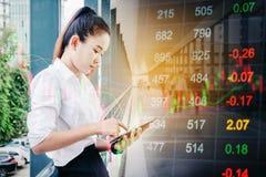 使用在数字式股市fi上的亚裔女商人智能手机 免版税库存图片