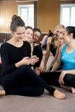 使用在断裂的小组愉快的运动的妇女手机在体育 免版税图库摄影