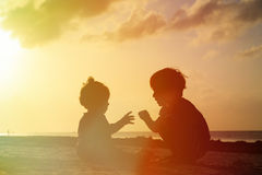 使用在日落的小男孩和小孩女孩 免版税库存图片
