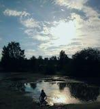 使用在日落的水坑的孩子 免版税库存图片