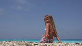 使用在日落的海滩,在海水的微笑的女孩投掷的小卵石的孩子 股票录像