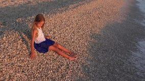 使用在日落的海滩,在海水4K的微笑的女孩投掷的小卵石的孩子 影视素材