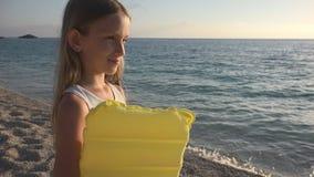 使用在日落的海滩,孩子观看的海波浪,在日落的女孩景色的孩子 库存图片