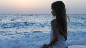 使用在日落的海滩,孩子观看的海波浪,在日落的女孩景色的孩子 股票视频