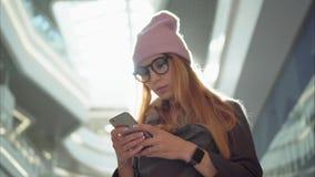 使用在智能手机的一位年轻行家女性app在大购物中心 股票录像