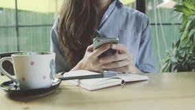 使用在智能手机的妇女app在微笑和发短信在手机的咖啡馆饮用的咖啡 美丽的年轻偶然女性professio 免版税库存照片