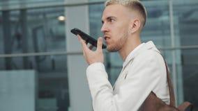 使用在智能手机的年轻商人企业应用程序走在城市在机场附近 他传送语音留言 英俊的年轻人 股票视频