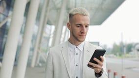 使用在智能手机的年轻商人企业应用程序走在城市在机场附近 生意人英俊的年轻人 股票视频