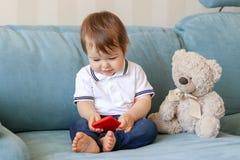使用在智能手机的逗人喜爱的微笑的男婴在家坐有玩具熊的沙发 免版税库存照片