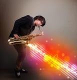 使用在有五颜六色的声波的萨克斯管的年轻人 图库摄影
