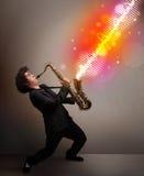 使用在有五颜六色的声波的萨克斯管的年轻人 免版税库存图片