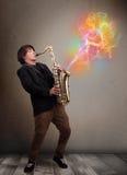 使用在有五颜六色的摘要的萨克斯管的可爱的音乐家 免版税库存图片
